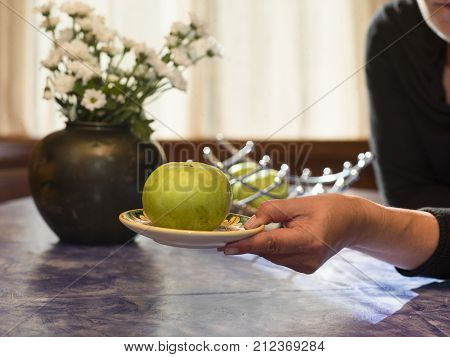 An apple laid on a plate in female hand contra light indoor shot
