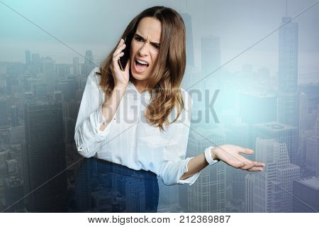 Nervous breakdown. Unhappy angry young woman talking on the phone and shouting at her interlocutor while being stressed out