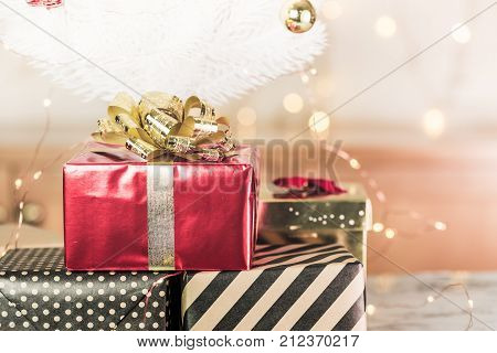 Red Glossy Present Box With Golden Bow And Ribbon Lay Under White Christmas Tree On White Marble Flo