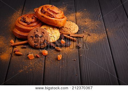 Two lush buns with cherries and a few oatmeal and chocolate cookies, black chocolate, nuts, raisins and a few cinnamon sticks of a wooden table. Around is sprinkled with grated cinnamon. Inside. View from above.