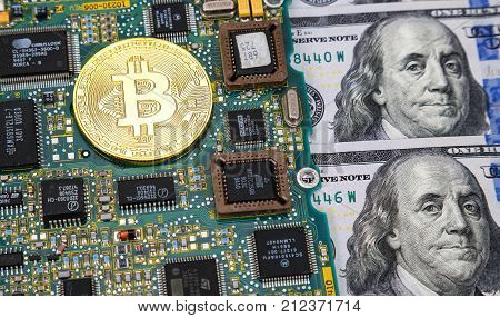 Moscow Russia - November 5 2017: Golden bitcoin lying over electronic computer component with american dollars