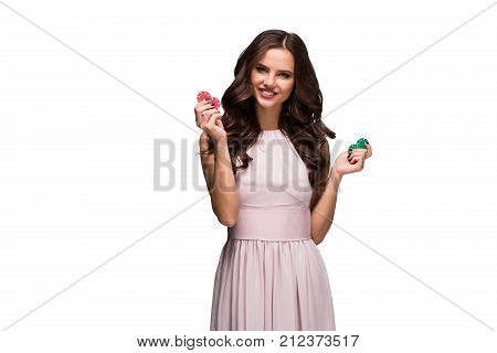 Sexy woman in a chic gently pink dress holding colored poker chips. Isolated on white background. Woman winning. Casino. Poker. Victory. Luck Roulette Blackjack Spin. Big win emotions