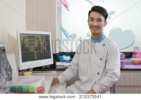 Male dentist sit beside computer screen while explain about oral and teeth issue. Dental care and healthy maintenace with expert concept