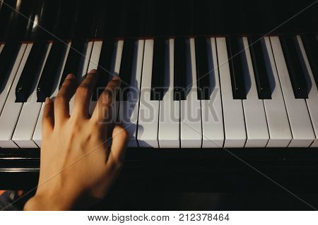 Young Woman Use Left Hand Play Piano Has Piano Key Are Background. This Image For Music, Artist, Art