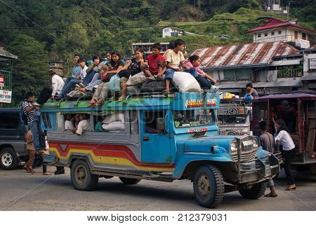 Banaue Philippines - June 17 2009: Typical Jeepney overloaded with passengers near Banaue North Luzon, Philippines. Jeepneys are both cheap public transportation and the symbol of Philippine culture and art