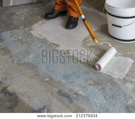 Worker puts primer with roller on concrete floor. Apartment under construction