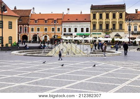 Brasov Romania October 06 2017 : Tourists walk near the fountain in the Square of Council Market around the Historical Museum and see the sights in the Old Town of Brasov in Romania