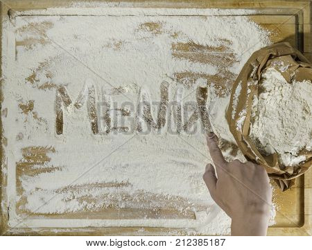 Rough wooden rectangular used cutting board background with paper sack of flour and menu word inscribed with finger directly from above