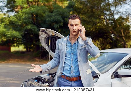 Man Stands Next To A Broken Car Calling