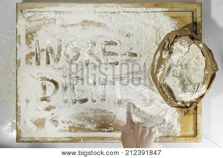Rough wooden rectangular used cutting board background with paper sack of flour and ingredients word inscribed with hand directly from above on white background