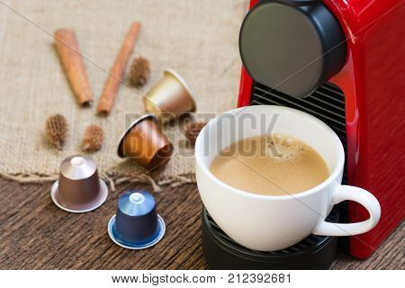 Espresso coffee machine with capsules making coffee in a white cup on the wooden table.