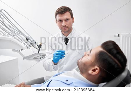Shot of a mature male dentist at work preparing to examine teeth of his male patient clinic office hospital dentistry professionalism healthcare medicine examination checkup dental concept. poster