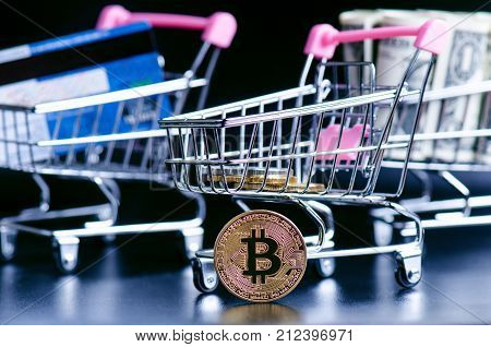 Bitcoin, bank card and money in a trolley on a black background. Concept of shopping and money. Cryptocurrency. Online shopping. Virtual currency and business.
