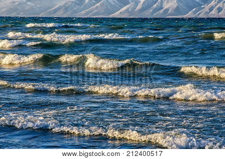 frozen sea view with mountans. Waves hitting icy coastline