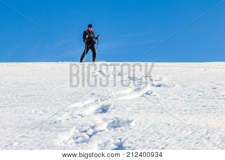Man is hiking with snoeshoes and hiking sticks through deep snow by following footprints