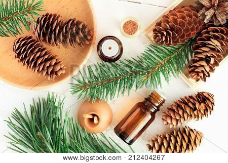 Wood scents for winter time aromatherapy. Pine cones and fresh green fir tree boughs, essential oil bottles, top view.