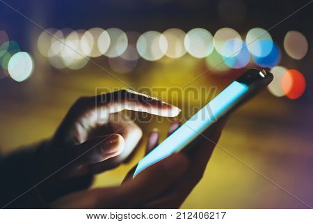 Woman pointing finger on screen smartphone on background illumination bokeh light in night atmospheric city hipster using in hands mobile phone closeup mockup glitter street in Barcelona online wifi internet concept