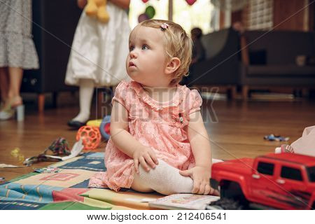 little baby girl with a big car sitting on floor