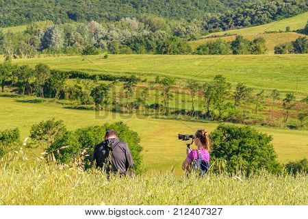 PIENZA ITALY - MAY 21 2017 - A couple taking pictures of their travel in Tuscany in the Natural Area of Val d'Orcia.