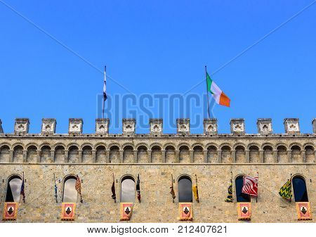 SIENA ITALY - JULY 2 2017 - The flags participating in the Palio di Siena exhibited in the palace of Rocca Salimbeni headquarters of the bank Monte dei Paschi di Siena.