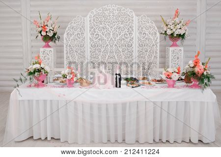 Decorated in white and pink tones wedding buffet table with tasty dishes on the indoors background of white wall