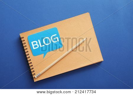Notebook with word BLOG on color background