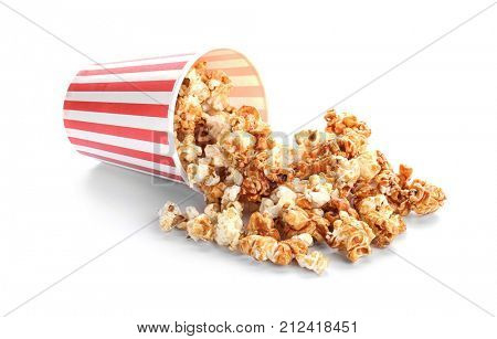 Overturned cup with tasty caramel popcorn on white background