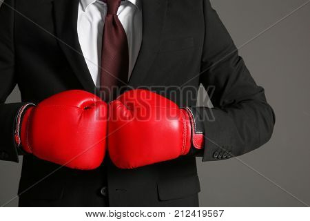 Businessman in boxing gloves on grey background