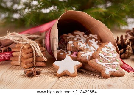 Christmas gingerbreads. Christmas decorations. Handmade cookies in paper cone  lying on the wooden table.  Christmas and New Year treats.