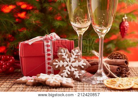 Two glasses with champange, fir tree, gift boxes and christmas ginger cookies on a red background. New year and Christmas.