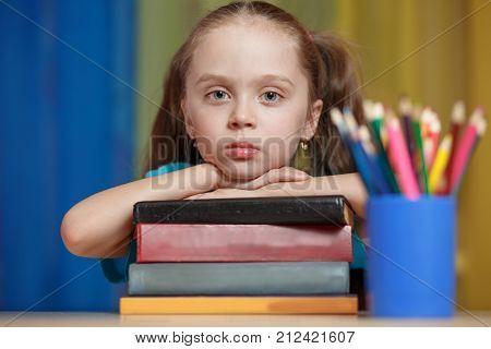Little girl holding pile of books. back to school