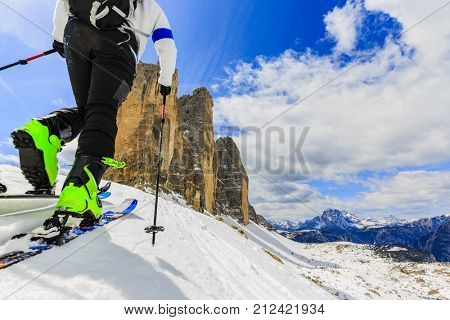 Mountaineer backcountry ski spring walking up along a snowy ridge with skis in the backpack. Tre Cime, Drei Zinnen in South Tirol, Dolomites, Italy. Adventure winter extreme sport.