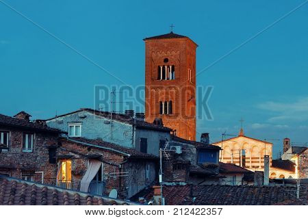 Tower of Chiesa San Pietro with roofs of historic buildings in Lucca at night, Italy.