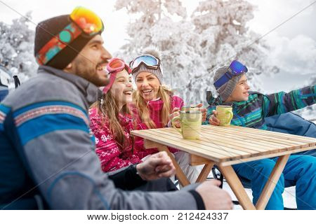 Family laughing and takes tea break during skiing on the mountain together