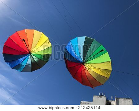 Colorful umbrellas in the air against a blue sky