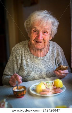An elderly woman eating lunch sitting at the table.
