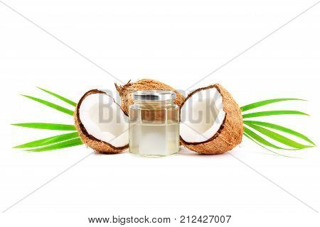 Whole and cut in half fresh coconuts with palm leaves and coconut water isolated on white background