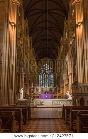 Sydney Australia - March 23 2017: Chancel with purple-dressed altar gothic tabernacle white statues and large stained window in back. Rather dark alcove like setting. Benches and pulpit in front.