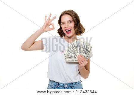 Portrait of a smiling happy girl holding bunch of money banknotes while showing ok gesture and looking at camera isolated over white background