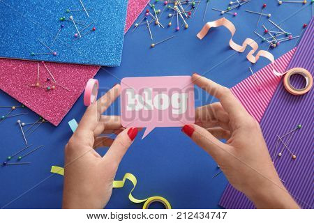 Woman holding dialog cloud with word BLOG against color background