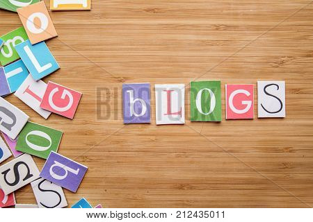 Word BLOGS on wooden background