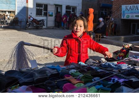 OLGIY, BAYAN-OLGIY, MONGOLIA - SEP 29, 2017: Unknown little girl in the city market sells jerseys. In Bayan-Olgiy province is populated to 88,7% by Kazakhs.