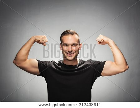 Handsome fit man tightening his muscles, showing his strength and power. Smiling, muscular attractive man in a studio portrait