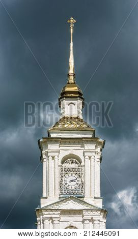 High gold Church steeple with a clock on the background of a stormy sky.