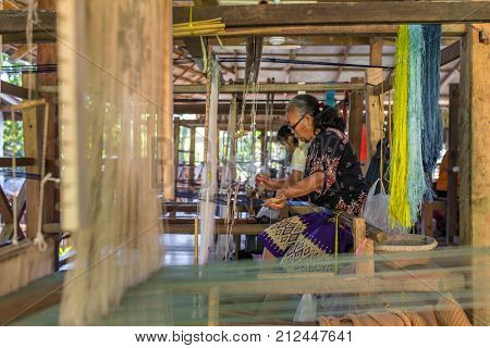 Luang Prabang - January 24, 2017: Unidentified woman weaving silk in Luang Prabang, Laos. Silk production factory.