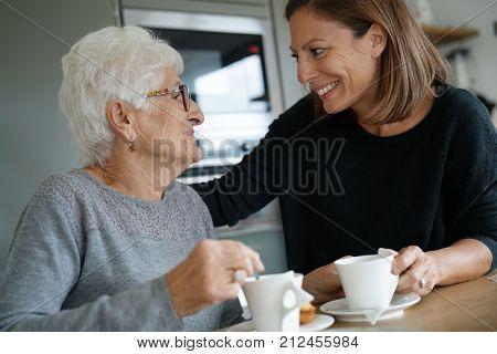 Homecarer serving tea to elderly woman