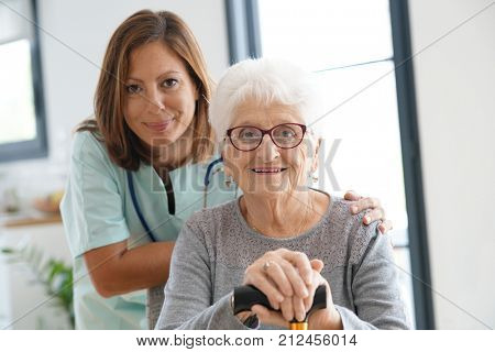 Nurse visiting old woman at home