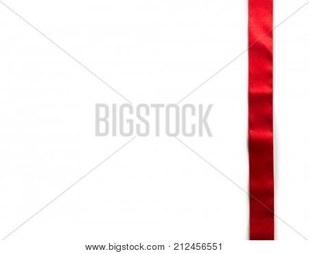 Simple vertical red ribbon with typical ripples or wrinkles of a silky or satin ribbon , isolated on white. highlight on upper half.