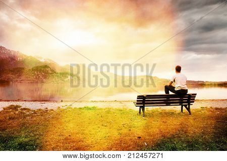 Tired Man In Blue Shirt Sit On Old Wooden Bench At Mountains Lake Coast.