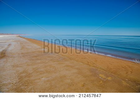 Sand coast of dying Aral sea in Kazakhstan at summer day. Empty sandy beach. Ecologic catastrophe of Aral sea.